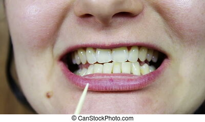 pick food from teeth with toothpick - girl picking with...