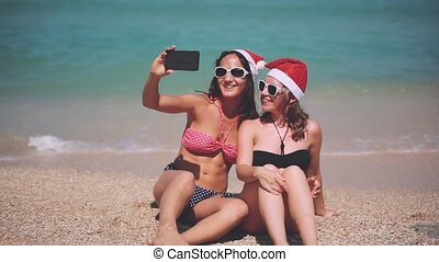Happy santa girls wearing santa hat on a sunny beach taking a selfie with smartphone having fun. Christmas modern technology concept. 1920x1080