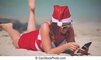 Christmas young smiling woman in red santa hat uses...