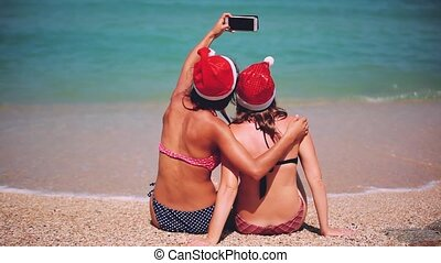 Happy santa girls wearing santa hat on a sunny beach taking a selfie with smartphone. Christmas modern technology concept. 1920x1080
