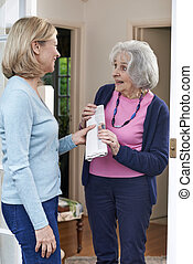 Woman Delivering Newspaper To Elderly Neighbour