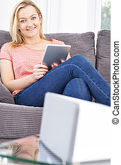 Woman Streaming Music From Digital Tablet To Wireless...
