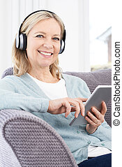 Mature Woman Streams Music From Digital Tablet To Wireless...