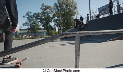Young man does slide trick on skateboard in the skatepark in...
