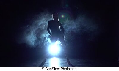 Dancing girl in latin style, in the haze. Slow motion -...