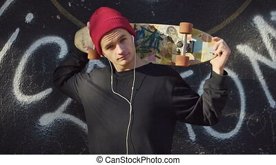 Teenager with a skateboard before graffiti wall