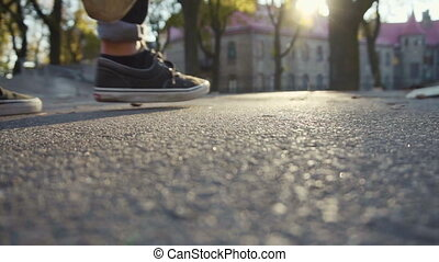Young man walking with skateboard - Sunset shot of a young...