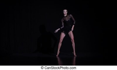Woman dancing latina elements in the studio, black background. Slow motion