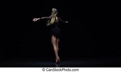Girl dancing ha-cha-cha in the studio, black background....