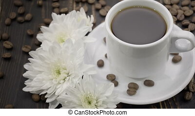 chrysanthemums and coffe on the wooden table -...