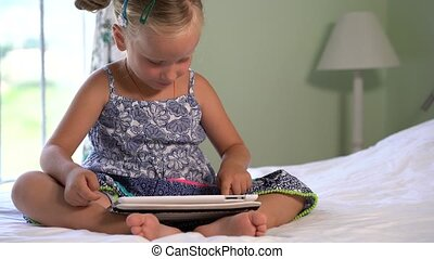 little cute girl plays a game on the tablet