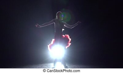 Girl dancing latino on a dark background with light...