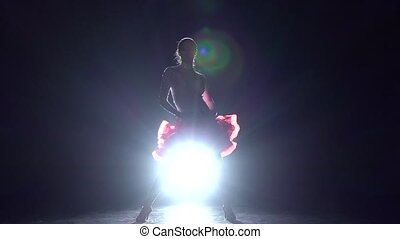 Girl dancing samba on a dark background with light...