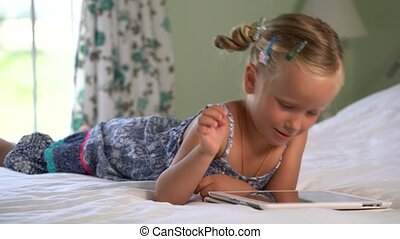 little cute girl plays a game on the tablet lying on the bed