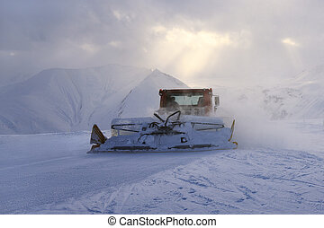 snowcat rides to work in the evening at sunset