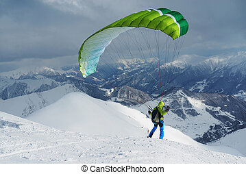 green skier starts with a paraglider in highlands - green...