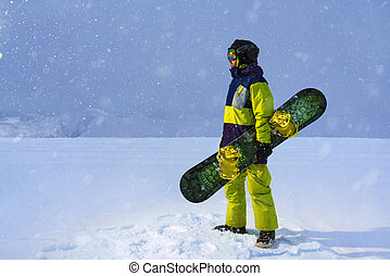 Snowboarder carries a board in hands. Evening snowfall in...