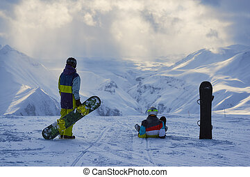 Snowboarders have a rest and look at winter mountains...