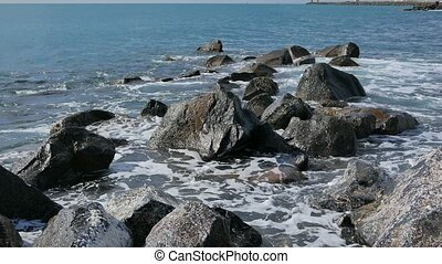 Waves crashing against the rocks. Ostia, Italy