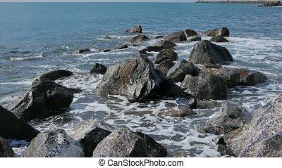Waves crashing against the rocks. Ostia, Italy
