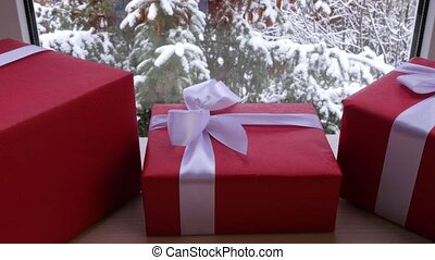 three box of gift on the table in front of the window in the...
