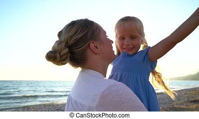 Mother twists daughter in her arms at sunset, slow motion