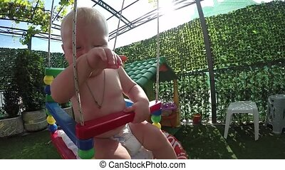 seven-month toddler for the first time on a swing