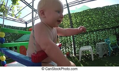 seven-month toddler for the first time on a swing, slow...