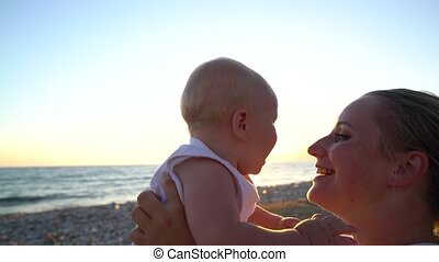 Mom coddling with a baby sitting on the beach at sunset
