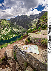 Orientation in mountains in summer with compass nad map,...