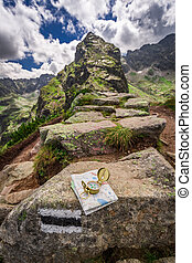 Orientation in mountains in summer with map and compass,...