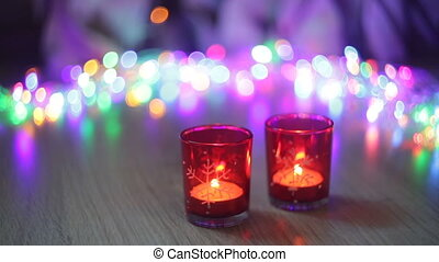 two red candlestick and multi-colored lights in the...