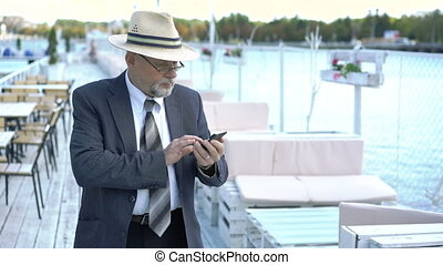 Senior man is using a mobile phone in open cafe. 4K