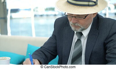 Handsome executive old man sitting at desk and writing the...