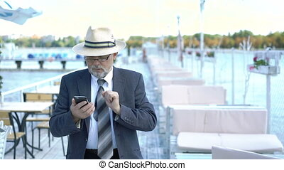 Elderly businessman calling on phone on the open cafe near sea. 4K