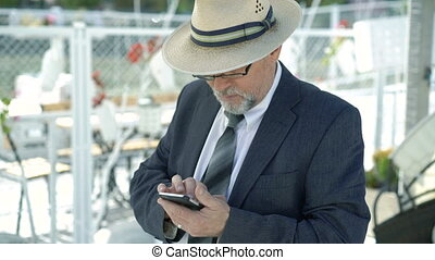 Portrait of stylish old man in hat using mobile phone. 4K