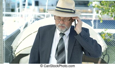Mature businessman talking on phone outside. 4k.