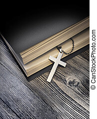 Metal cross on top of a black book cover on wooden...