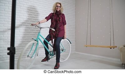 Girl sitting on retro bicycle in studio