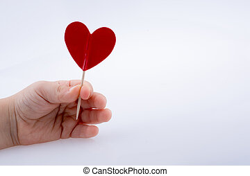 Little red color heart shape in hand - Little red color...