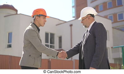 Two businessmen meet and shake hands near busy modern office building. 4K