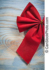 Red Christmas bow on wooden board directly above...
