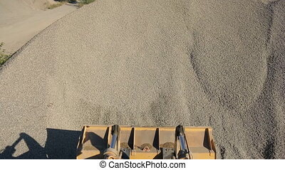 Orange excavator bucket scoops up crushed stone, view of...