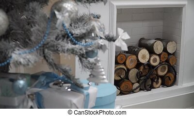 Close-up firewood in the fireplace at Christmas tree with...