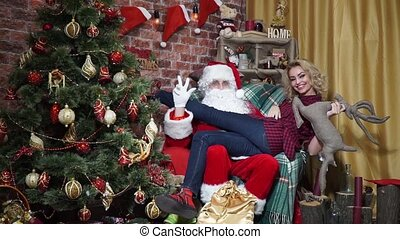 Sexy girl is sitting on the lap of Santa