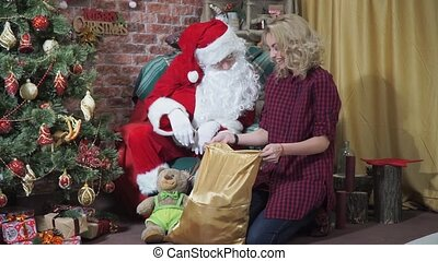 Santa and girl stares into the bag with gifts