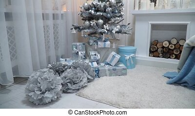 Closeup, gifts under the Christmas tree in the fireplace