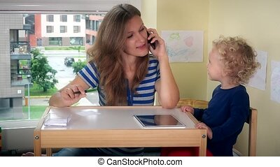 Mother call phone and help child girl play with tablet. Business woman work