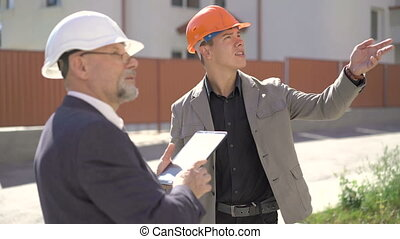 Two architects are discussing in construction helmets and using tablet. 4K