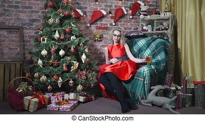 Sexy girl sitting in a chair near a Christmas tree